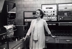 Alice Shields smiling and looking towards audio equipment